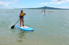People paddle boarding in mission bay in Auckland New Zealand Stock Photos
