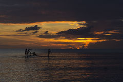 People paddle boarding during sunset Stock Photography