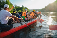 People paddle oars, russian water tourism. People paddle oars together, russian water tourism Stock Photography