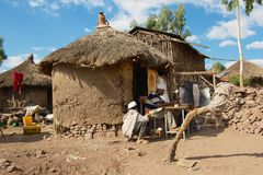 People paint and read at the house entrance in Lalibela, Ethiopia. LALIBELA, ETHIOPIA - JANUARY 27, 2010: Unidentified people paint and read at the house Stock Image