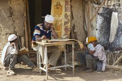 People paint and read at the house entrance in Lalibela, Ethiopia. Royalty Free Stock Photo
