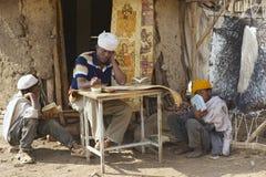 People paint and read at the house entrance in Lalibela, Ethiopia. LALIBELA, ETHIOPIA - JANUARY 27, 2010: Unidentified people paint and read at the house Royalty Free Stock Photo