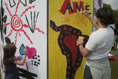 People Paintintg Wall. Celebration of the World Fair Trade Day People Painting Wall,  Fair Trade Theme,  on the Lawn at La Villette Park, to encourage people to Royalty Free Stock Images