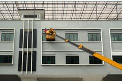 People paints a building on a yellow crane. / City/ Construction stock images
