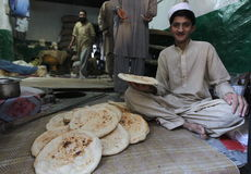 People in Pakistan - a daily life. A boy selling a bread at the shop in Swat Valley, Pakistan Stock Image