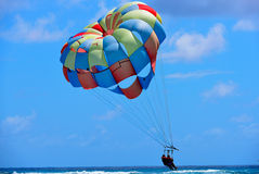 People on the parachute above the sea. People a colorful parachute over the Caribbean sea royalty free stock photography