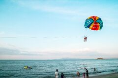 People paragliding on beach over sea Stock Photo