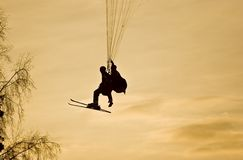 People on paraplane at sunset. Silhouette of two people on powered parachute or paraplane at sunset, traveling over trees Stock Image