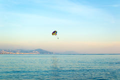 People parasailing over the sea at sunset Stock Images
