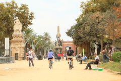 People in park by Arc de Triomf in Barcelona. People in park by Arc de Triomf - some riding on bicycles, some walking and having rest and one man making soap Stock Photography