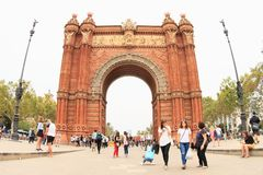 People in park by Arc de Triomf in Barcelona. People in park by Arc de Triomf - some riding on bicycles, some walking and having rest and one man making soap Stock Photos