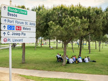 Road sign and people in park in Barcelona Stock Images