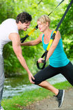 People in park on suspension or sling trainer Stock Images