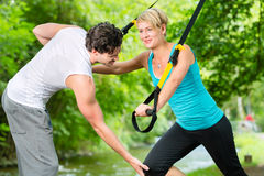 People in park on suspension or sling trainer Royalty Free Stock Image