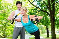 People in park on suspension or sling trainer Stock Photography