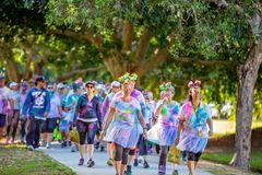 People Participating In Color Frenzy Fun Run. MACKAY, QUEENSLAND, AUSTRALIA - JUNE 2019: Unidentified people splashed with colored powder walking in Color Frenzy royalty free stock image