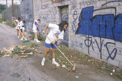 People participating in community cleanup. A group of young people participating in community cleanup by sweeping an alley royalty free stock photos