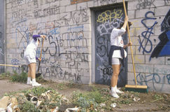 People participating in community cleanup. A group of young people participating in community cleanup by sweeping an alley stock photography