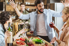 People partying at kitchen. Young people partying at kitchen, drinking wine, having food at home party Royalty Free Stock Photography