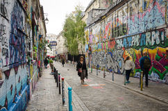 People pass by the azzling street art on Rue Denoyez in Paris Royalty Free Stock Images