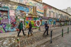 People pass by dazzling street art on Rue Denoyez in Paris Stock Photography