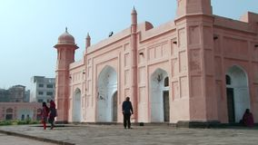 People pass facade of the Mausoleum of Bibipari in Lalbagh fort in Dhaka, Bangladesh. stock video footage
