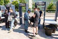 People pass through police frames metal detectors. Samara, Russia - May 12, 2017: People pass through police frames metal detectors at the city street in summer royalty free stock photo