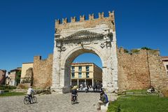 People pass under Augustus Arch - the ancient romanesque gate and the historical landmark of Rimini, Italy. RIMINI, ITALY - MAY 13, 2013: Unidentified people Royalty Free Stock Photos