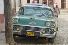 People pass vintage American car parked at the street in Trinidad, Cuba. Royalty Free Stock Photo