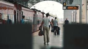 People passangers with bags walking along red train at railroad station stock video