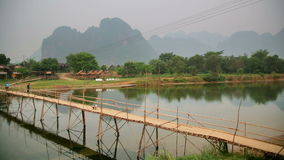 people passing bamboo bridge on limestone mountain background stock video footage