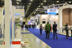 People passing on the blue floor coverings exhibition. Royalty Free Stock Photos