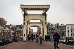 People passing the famous wooden drawbridge Magere Brug with buildings in the background in Amsterdam. AMSTERDAM, NETHERLANDS - NOVEMBER 22, 2018: Front view of stock photo