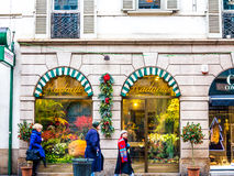 People passing by a flower shop. December 2013, Milan, Italy Stock Photography