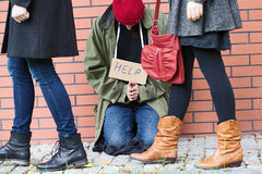 People passing by the homeless person stock photography