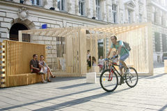 People Passing on Lipscani Street. Man riding a bicyle  passing on Lipscani Street besides Poiana lui Iocan architectural pavillion, during the Architectural Royalty Free Stock Photography