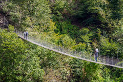 People passing over the hanging monkey bridge Stock Photo