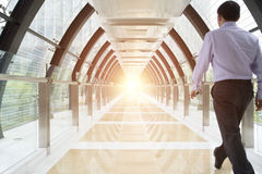 People passing tunnel building with glass wall Royalty Free Stock Photo