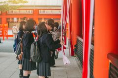 People pay homage throw coins and shake the bell to sacred blessings in the Japanese shrine. Kyoto, 13 November 2016 royalty free stock photography