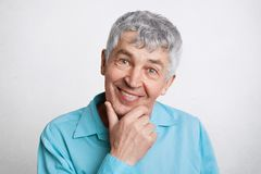 People, pension and positive emotions concept. Pleased mature male with grey hair, keeps hand under chin, wears formal blue shirt,. Looks confidently and Royalty Free Stock Image