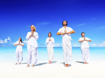 People performing yoga on the beach Peaceful Concept Royalty Free Stock Image