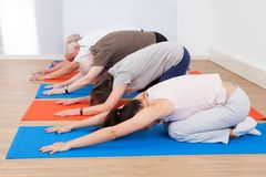 People performing yoga at gym Royalty Free Stock Images