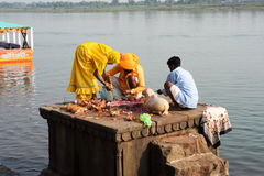 People performs pooja on sacred river Narmada in Maheshwar. Maheshwar, India - 3 February 2015: People performs morning pooja on sacred river Narmada ghats in Royalty Free Stock Image