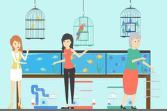 People at pet shop. Birds in cages, fish in aquariums and more Stock Images