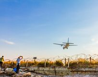 People photographing a turboprop airplane landing at Larnaca Int stock image