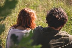People Photography of Man and Woman Sitting on Green Grass Field stock image