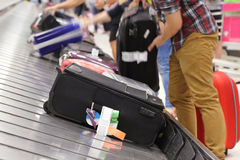 People picking up suitcase on luggage conveyor belt Royalty Free Stock Images