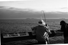 People on the Pier in California. Enjoy the people on the  pier in San Diego, California fishing with a white hat on Stock Image