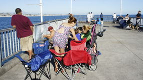 People at The Pier. People family men women children old young fishermen fisherwoman having fun of catching fish at the Pier together with their children Royalty Free Stock Images