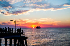 People on Pier Sillouetted with Freighter at Sunset Stock Photo
